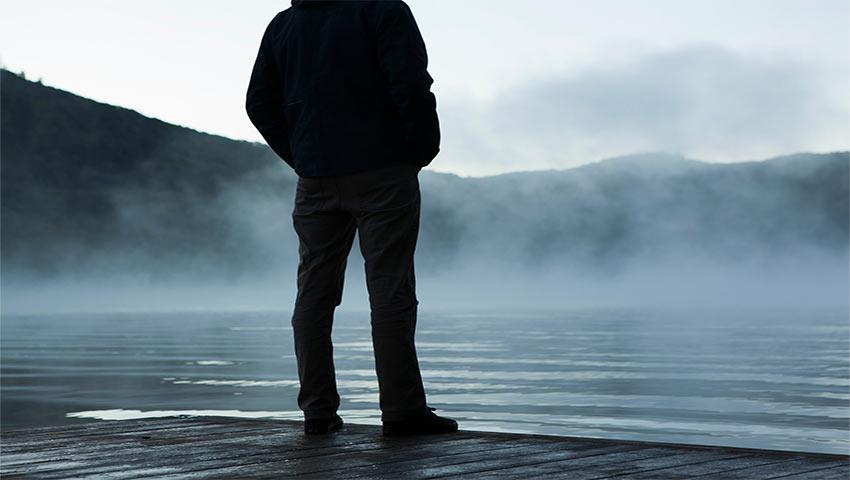 Человек стоит у кромки воды и думает о самоубийстве
